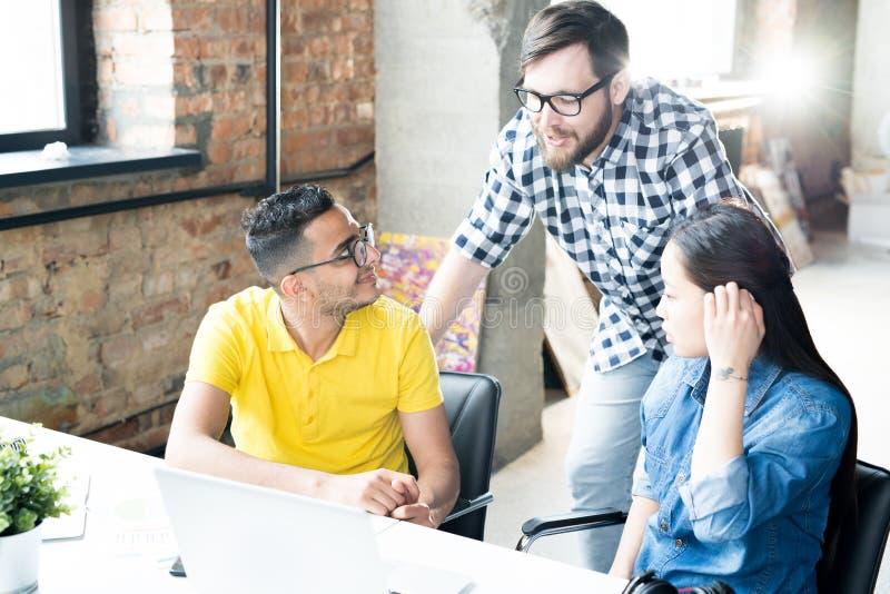 创造性的青年人谈论工作在办公室 库存图片