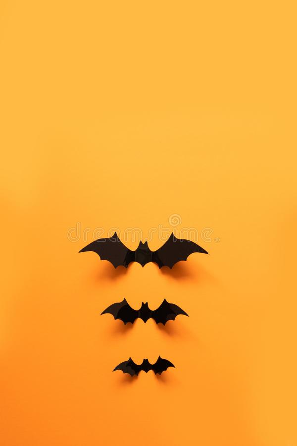 创造性的顶视图万圣节结构的黑纸棒飞行在橙色背景 库存图片