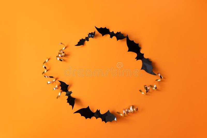 创造性的顶视图万圣节结构的黑纸棒飞行在橙色背景 图库摄影