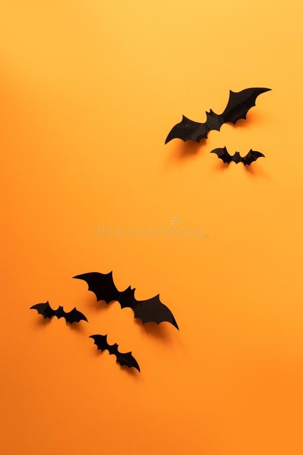 创造性的顶视图万圣节结构的黑纸棒飞行在橙色背景 库存照片