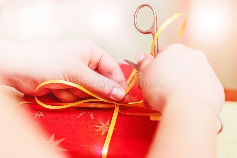 创造性的diy工艺爱好 做与剪刀的手工制造工艺丝带 有剪刀和红色礼物盒关闭的女性手 精选 免版税库存照片