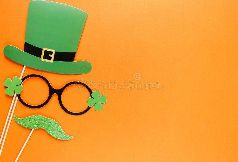 创造性的st帕特里克斯天橙色背景 爱尔兰假日庆祝的平的被放置的构成与照片摊装饰的:帽子,玻璃 免版税库存图片