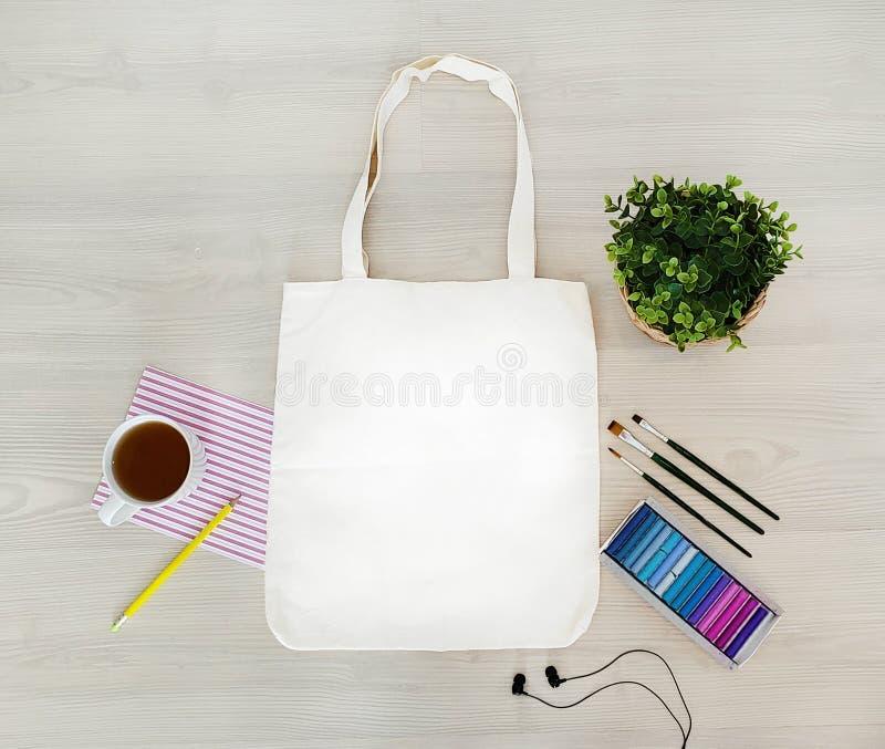 创造性,时髦,艺术性的eco,搬运,棉花袋子嘲笑 与耳机的大模型,铅笔,杯子,油漆,蜡笔,缨子 库存图片