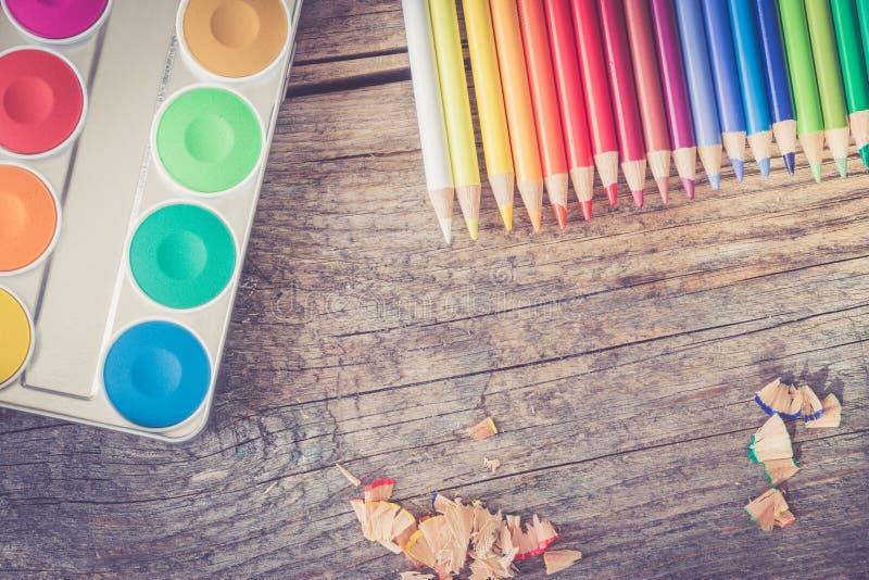 创造性:多彩多姿的铅笔、水彩和刷子在生锈的木桌上 免版税库存照片