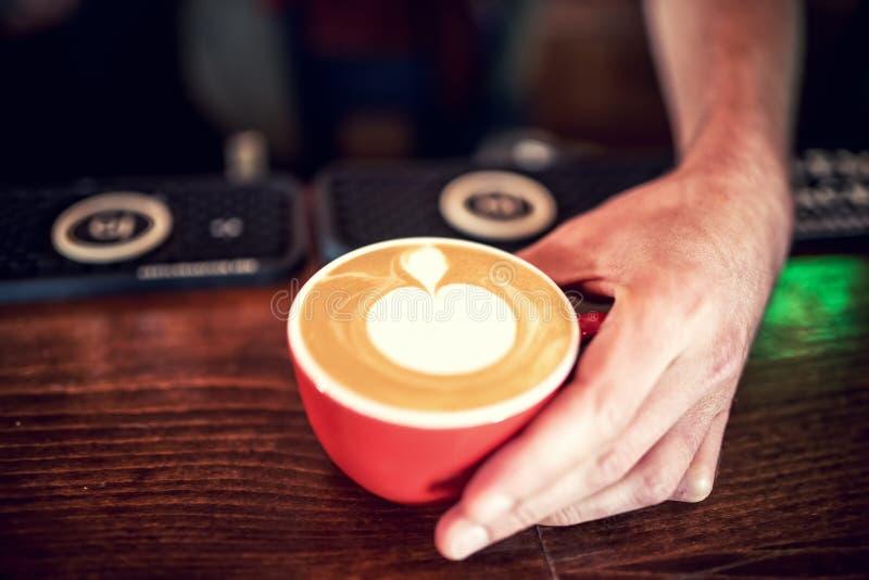 创造拿铁艺术的男服务员和barista用在新鲜的咖啡的牛奶泡沫 浓咖啡浓咖啡用牛奶在客栈服务 库存照片