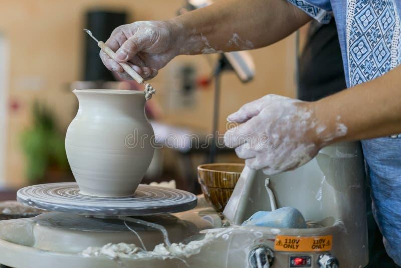 创造瓶子或花瓶白色黏土特写镜头 主要缸 做黏土水罐宏指令的人手 雕刻家在车间做a 库存照片