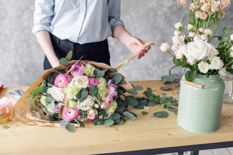 创造美丽的花束的妇女卖花人在花店 工作在花店 女孩助理或所有者在花卉 免版税库存图片