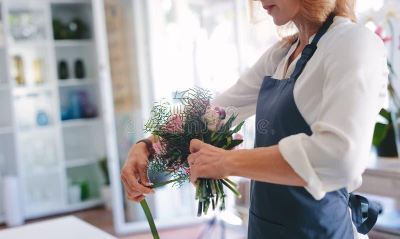 创造花束的纯熟女性卖花人 免版税图库摄影