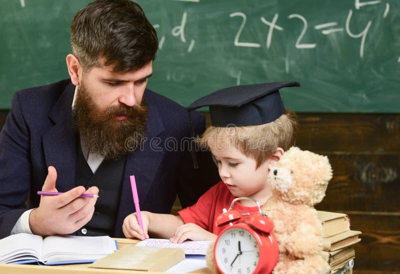 初级教育 礼服的灰泥板的老师和学生在教室,在背景的黑板 孩子 免版税图库摄影
