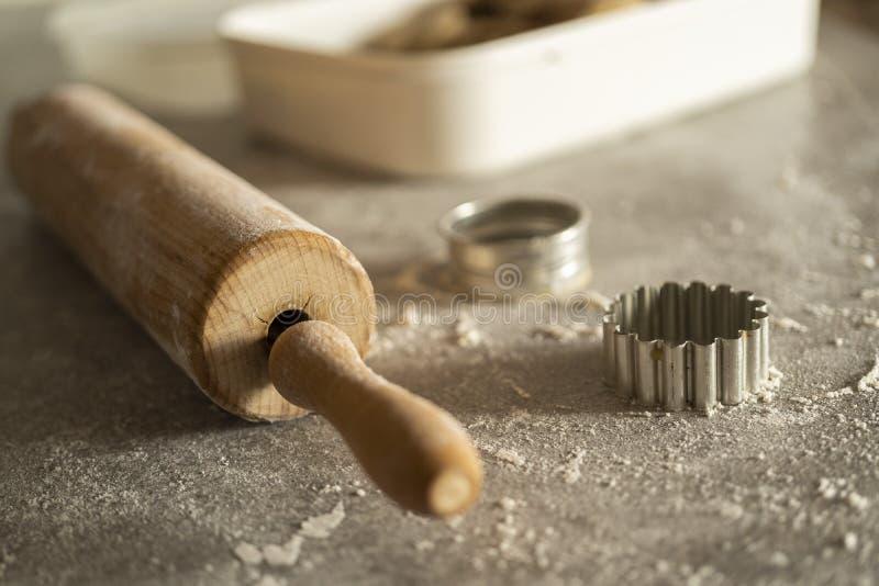 删去的饼干面团的曲奇饼一滚针和切开equitment在厨房用桌上的用很多面粉 免版税图库摄影