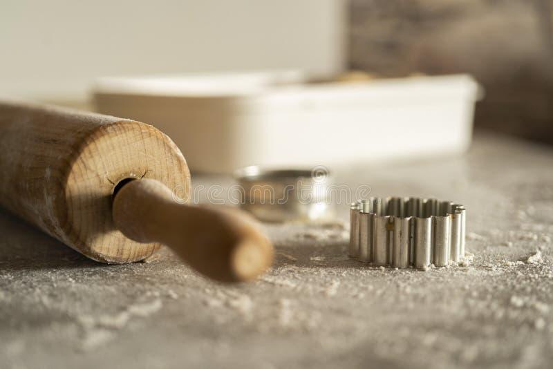 删去的饼干面团的曲奇饼一滚针和切开equitment在厨房用桌上的用很多面粉 免版税库存照片
