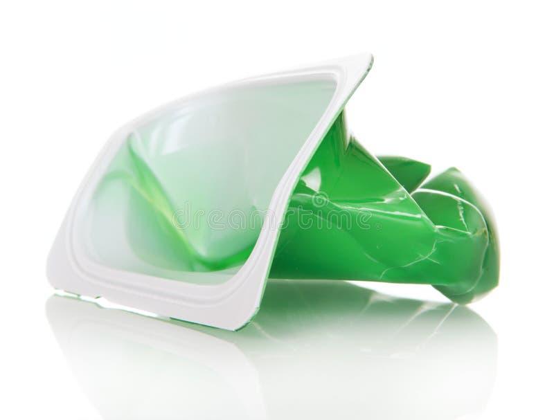 删去被弄皱的塑料杯子在白色的酸奶 库存图片