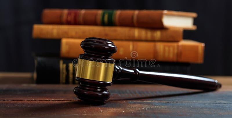 判断在一张木书桌上的惊堂木,法律书籍背景 免版税库存照片