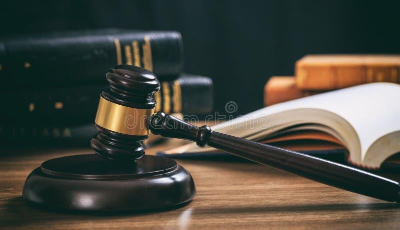判断在一张木书桌上的惊堂木,法律书籍背景 库存照片