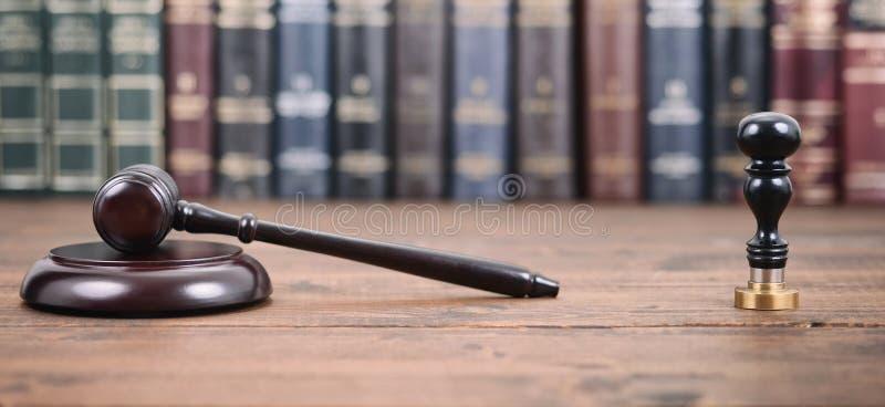 判断惊堂木,公证员封印和法律书籍在木背景 图库摄影