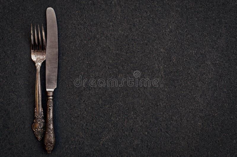 利器叉子和刀子黑表面上 免版税图库摄影