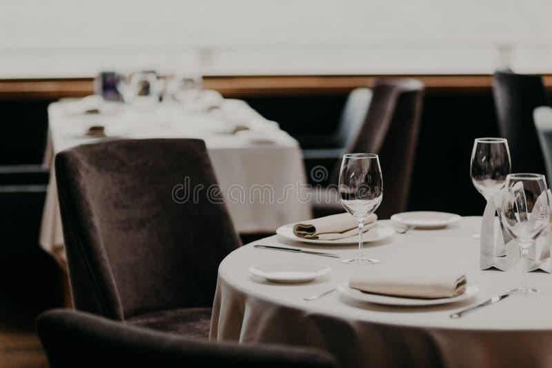 利器和酒杯在白色桌布,近空的扶手椅子 宴会大厅在餐馆 客人的服务的桌咖啡馆的 C 免版税库存照片