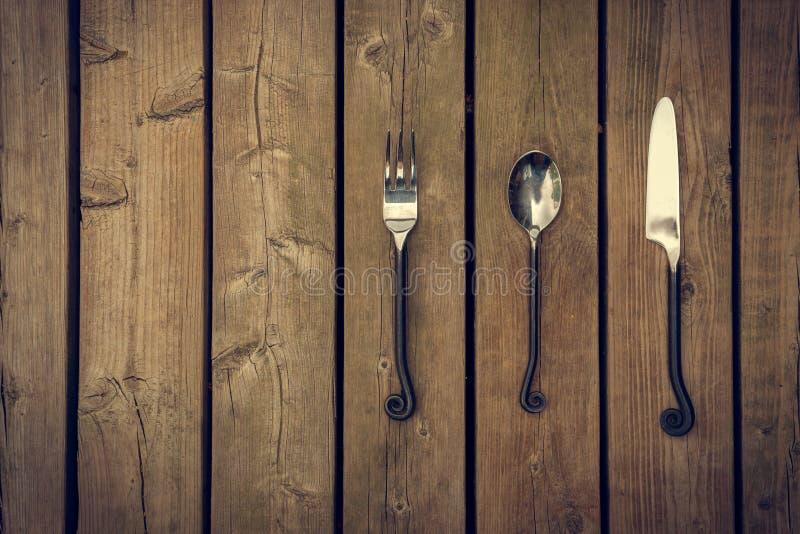 利器-叉子、匙子和刀子在木背景 库存图片