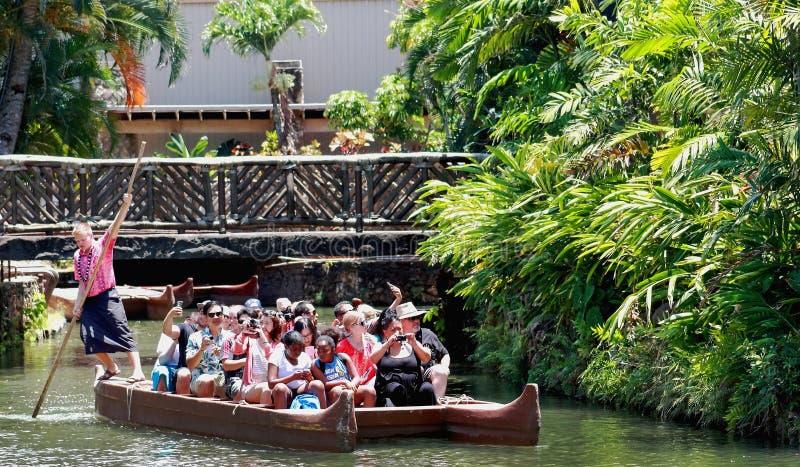 玻利尼西亚文化中心的访客用浆划在独木舟的小河下 免版税库存图片