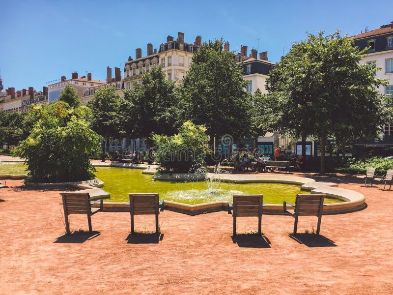 利昂,法国有放松的喷泉和地方的一个公园 在俯视水的半圆的四条长凳立场 rel的一个地方 免版税库存图片