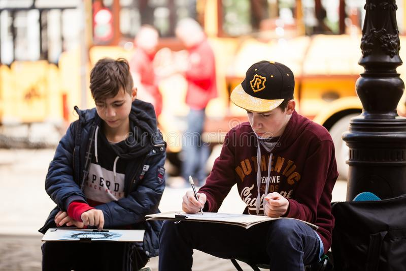 利沃夫州乌克兰- 2019年5月17日:两个男孩创造户外剪影 学习者绘老欧洲城市的都市风景 免版税库存照片