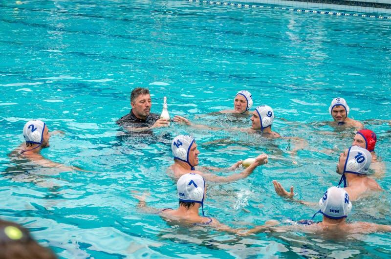 利沃夫州,乌克兰- 2015年7月:乌克兰水马球 运动员队的在游泳池的水球球和做攻击的射击  免版税库存照片