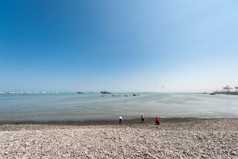利马,秘鲁- 2013年4月12日:与船和游艇的南太平洋海岸线 岸的三个人 库存图片