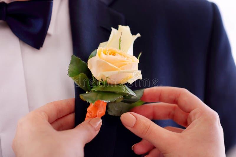 别住在婚礼gro衣服夹克的新娘玫瑰钮扣眼上插的花  免版税库存照片