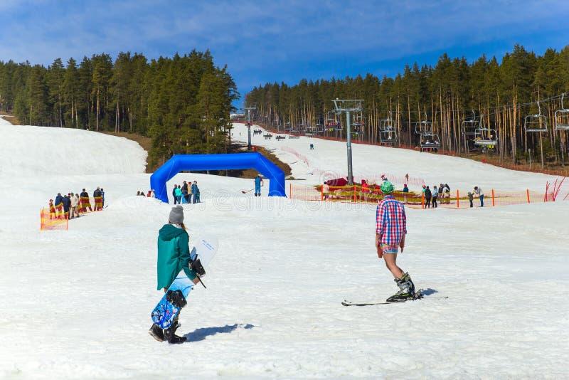 别洛列茨克,俄罗斯,2019年4月13日-年轻人乘坐穿滑稽的服装的雪板,结束在乌拉尔山脉的滑雪季节 库存图片