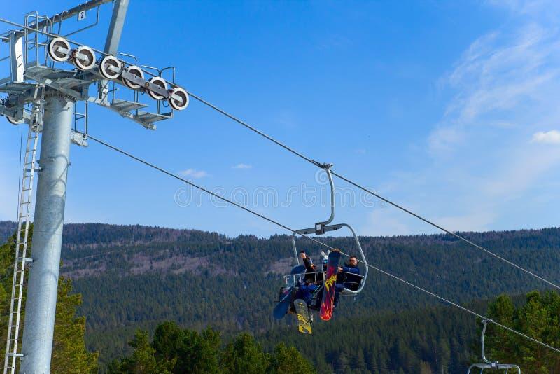 别洛列茨克,俄罗斯,2019年4月13日-有雪板的年轻人在滑雪电缆车去反对天空蔚蓝,结束滑雪季节  免版税库存照片
