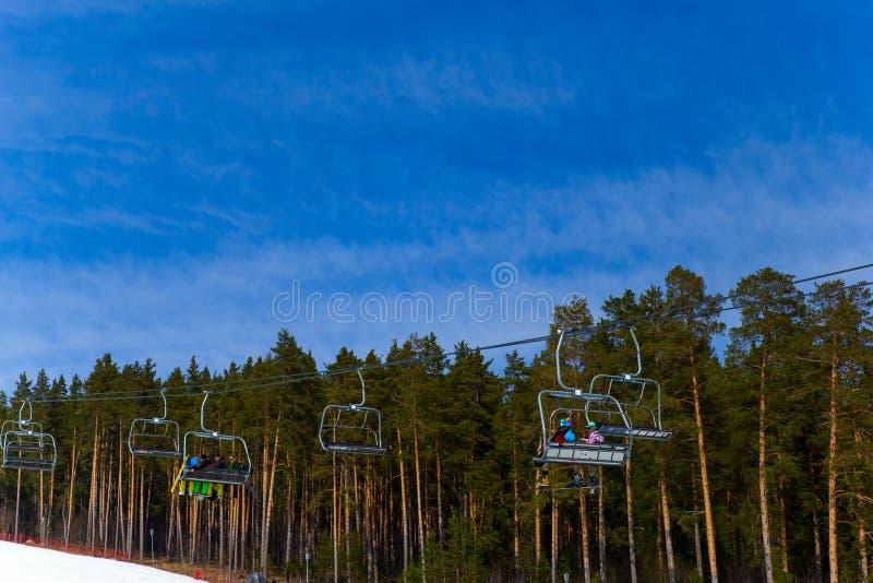 别洛列茨克,俄罗斯,2019年4月13日-滑雪电缆车的人们反对天空蔚蓝,结束在乌拉尔山脉的滑雪季节 免版税库存照片