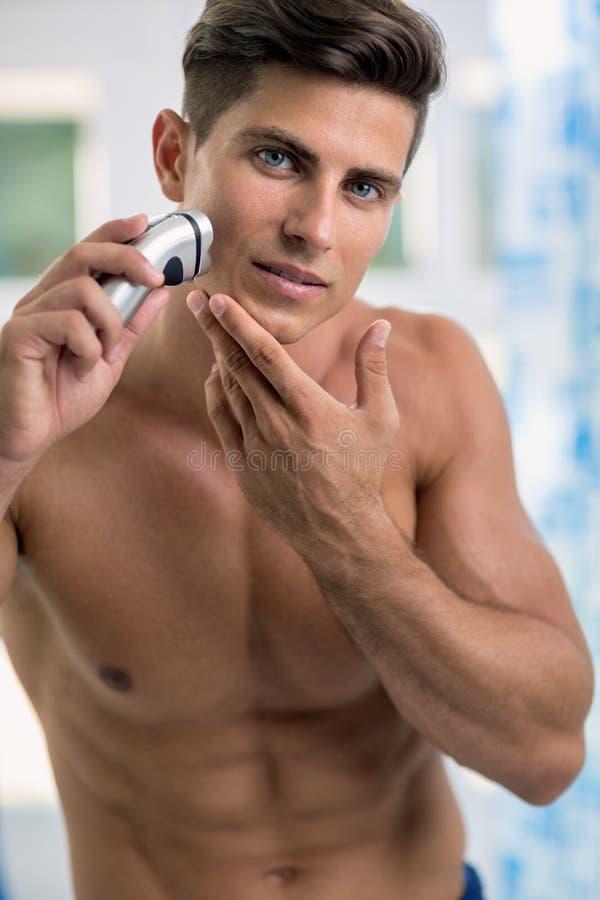 刮下巴和面颊的人画象由电动剃须刀 免版税库存照片