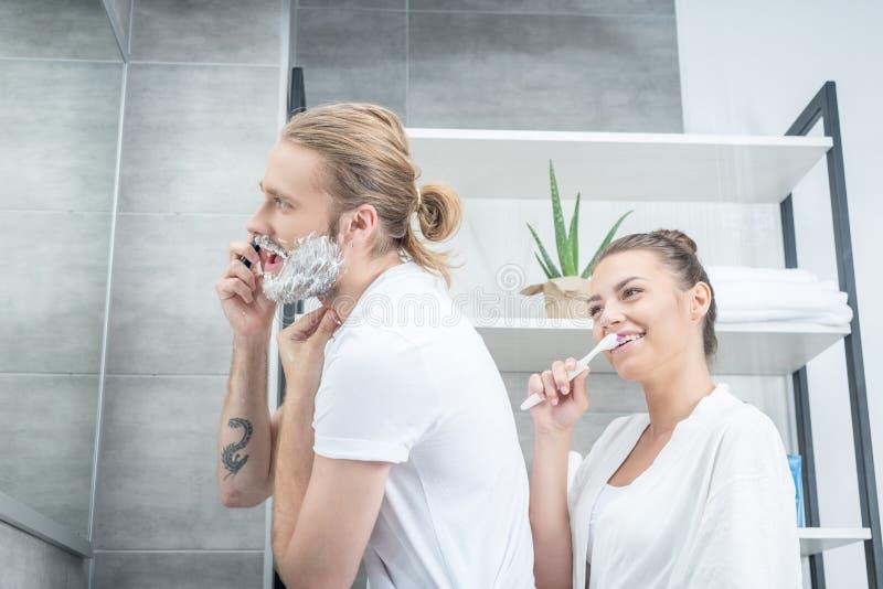 刮与剃刀和微笑的妇女掠过的牙的年轻人胡子在卫生间里 库存图片