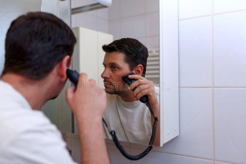刮与电动剃须刀的镜子的人 库存照片
