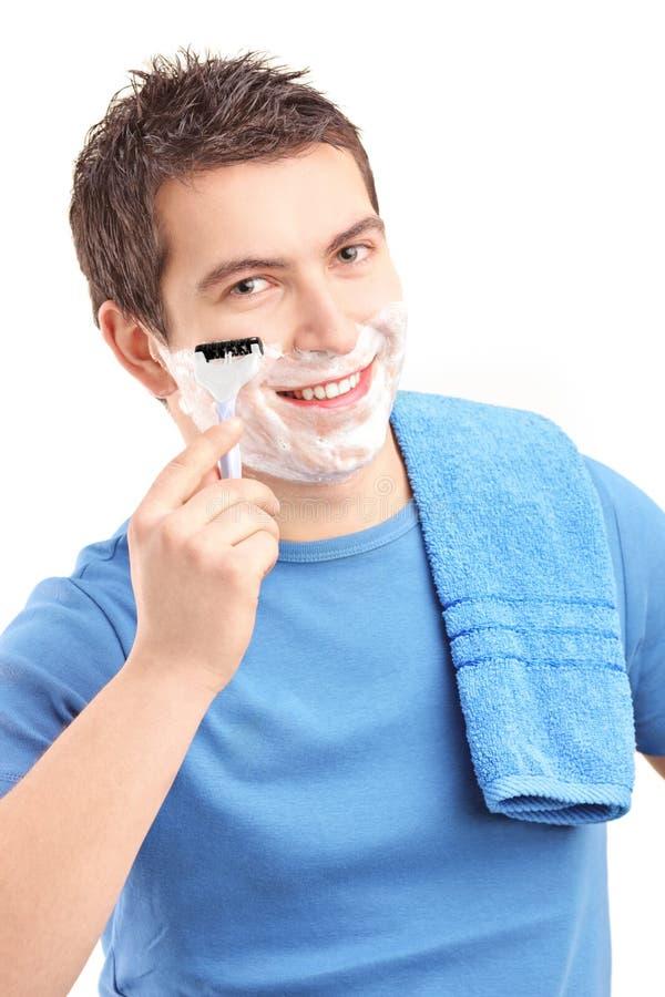 刮他的与剃刀的一个年轻人的纵向胡子 免版税库存图片