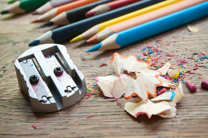 刮在木书桌上的磨削器和铅笔 库存照片
