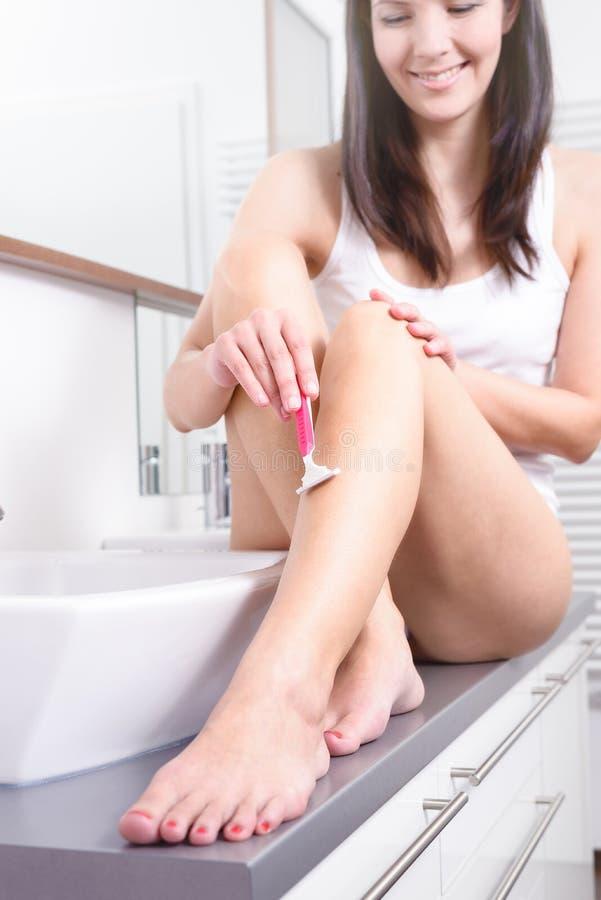 赤裸少妇露屄_刮在她的腿的微笑的美丽的赤裸少妇头发有一把桃红色一次性剃刀的坐