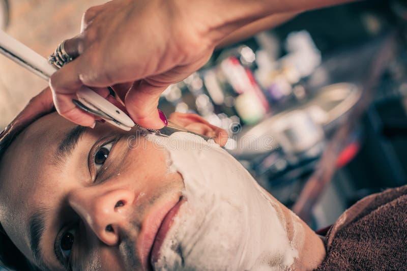 刮客户的女性理发师 免版税库存照片