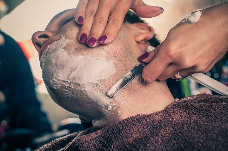 刮客户的女性理发师 免版税图库摄影