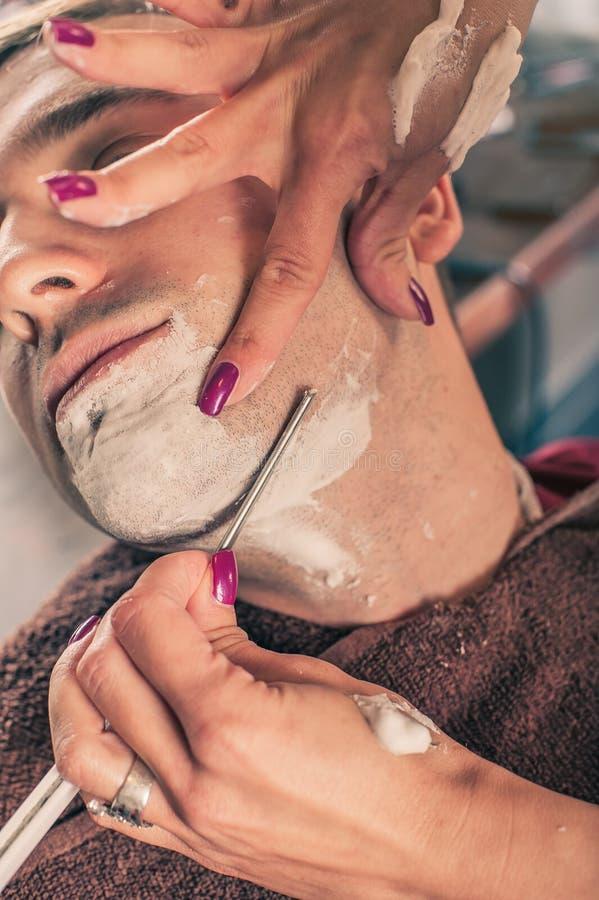 刮客户的女性理发师 免版税库存图片