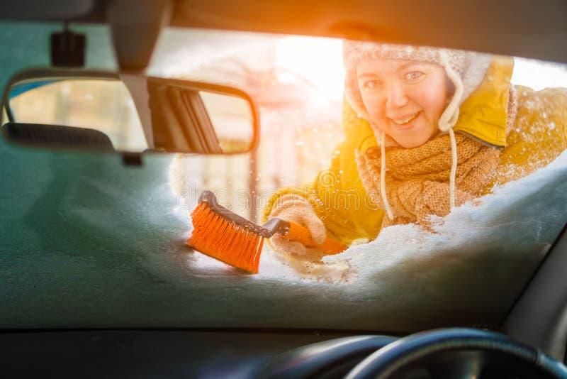 刮白种人的妇女和清洗雪汽车挡风玻璃 免版税库存照片
