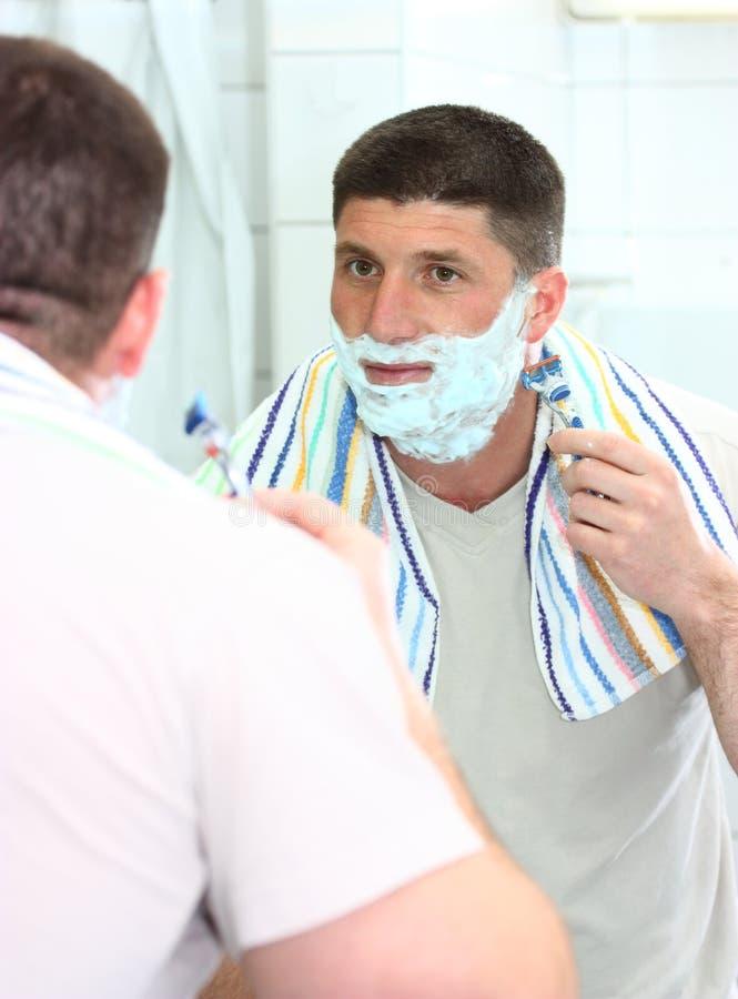 刮胡须他人刮 库存图片