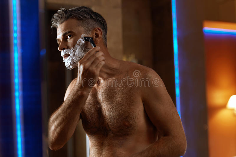刮面孔的英俊的人在卫生间里 面毛修饰 图库摄影