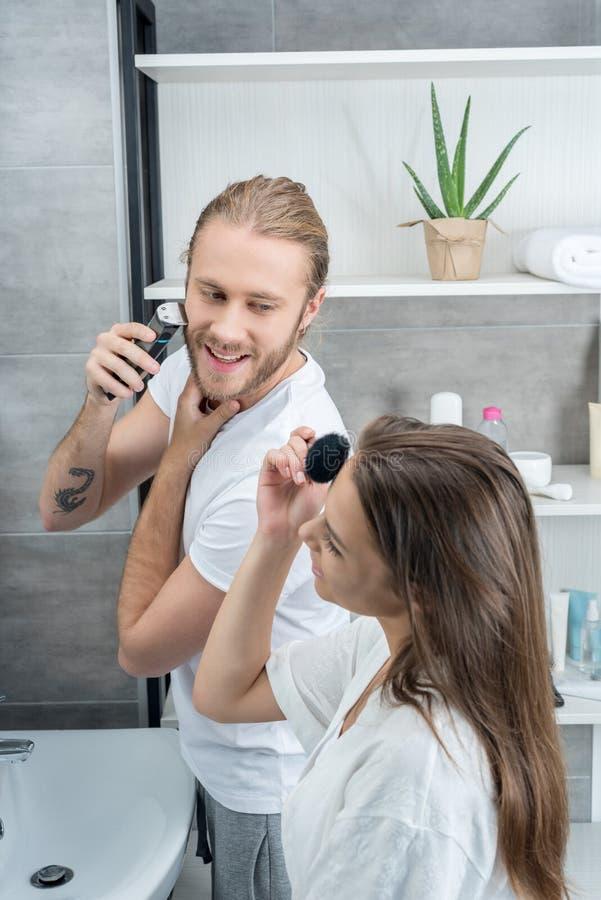 刮他的胡子的丈夫,当应用面粉的妻子在卫生间里早晨时 免版税图库摄影