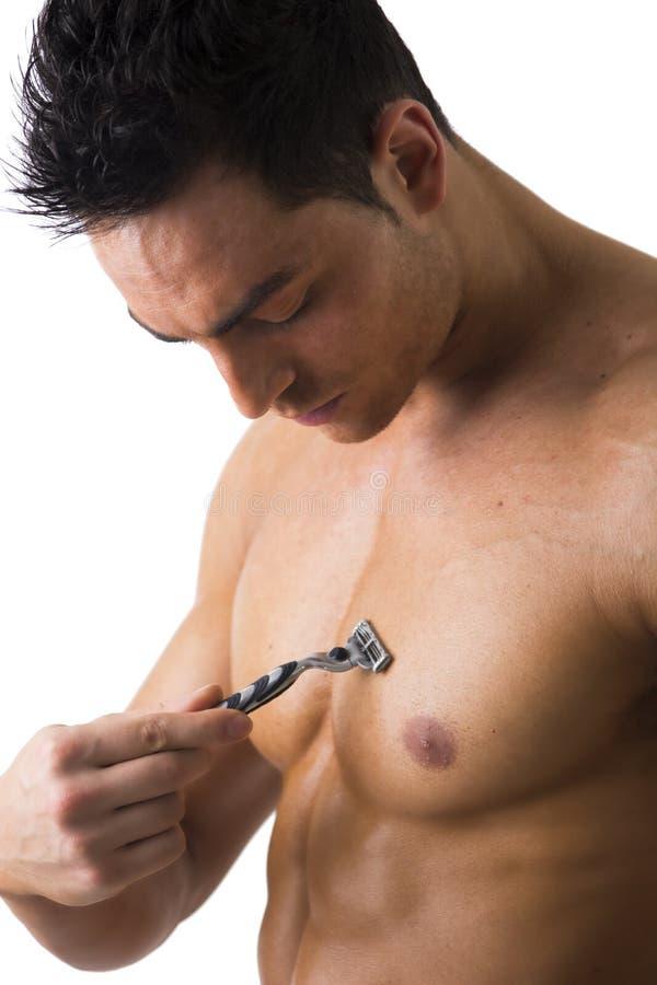刮他的胸口的英俊的肌肉的年轻人 图库摄影