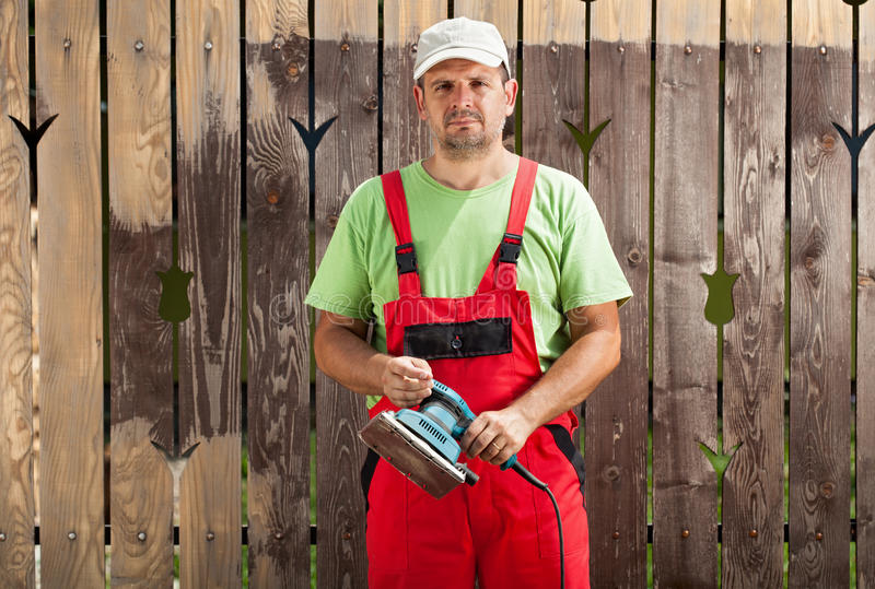 刮从篱芭的工作者人老油漆与电手工工具 免版税库存图片