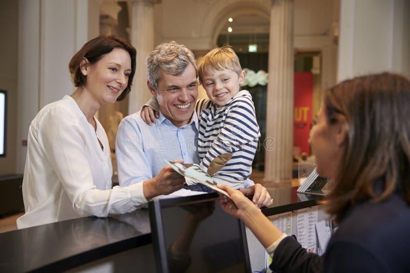 到博物馆的家庭买的词条票从招待会 免版税库存照片