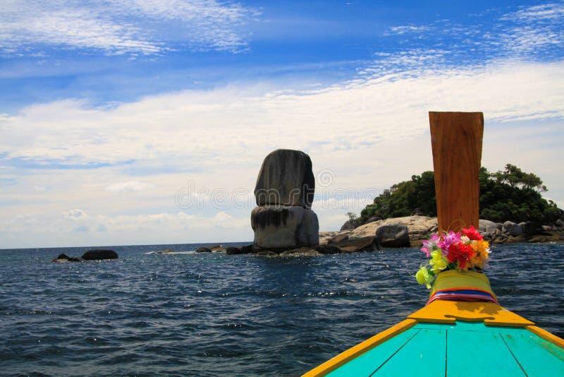 到被堆积的岩石的小船旅行反对与用花装饰的langtail小船弓的天空蔚蓝 免版税图库摄影
