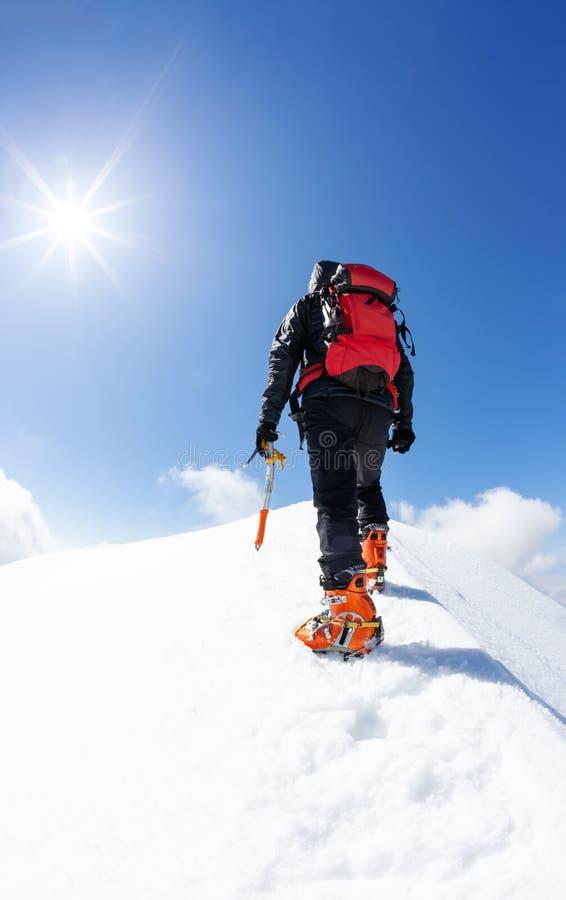 到达一个多雪的山峰的山顶的登山人 概念:克服患难,达到目标 免版税库存照片