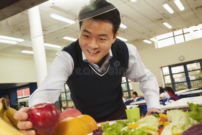 到达为健康食物的老师在学校食堂 免版税库存照片